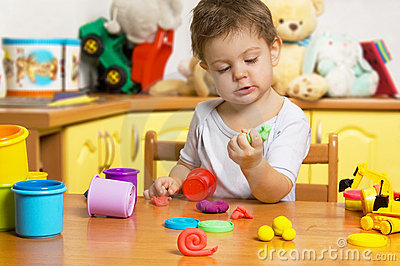 Little child playing plasticine