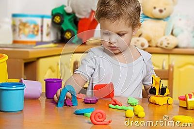 Little child playing plasticine