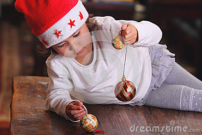 Little child plays with xmas tree decoration