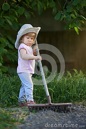 Free Little Child Raking Up Soil And Preparing For Planting Stock Photos - 54965173
