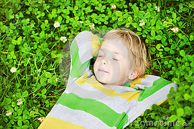 Little child sleeping outdoors on grass