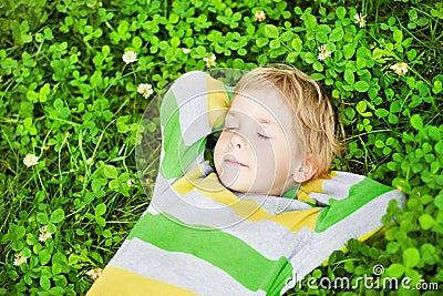 Little child sleeping outdoors on grass