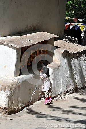 Little child on tiptoe to reach praying wheels Editorial Stock Photo
