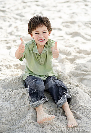 Little child with two thumbs up at the sea shore
