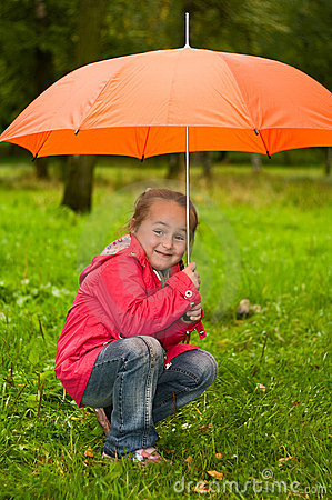 Little child under orange umbrella