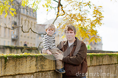 Little child and young father in autumn city