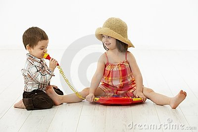 Little children playing with toy instrument