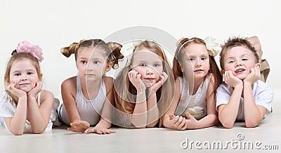 Little children in white clothes lie on floor