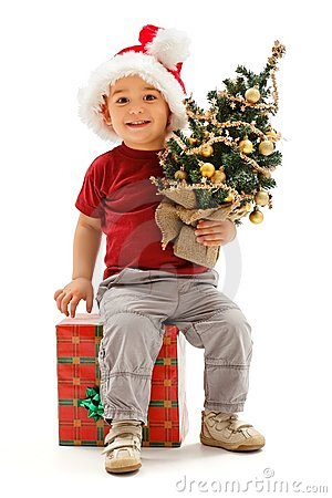 Little christmas boy sitting on present