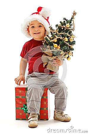 Little christmas boy sitting on present