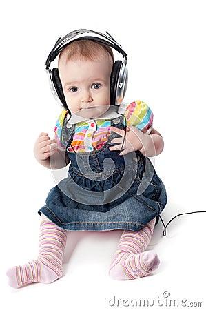 Little cute baby girl in headphones