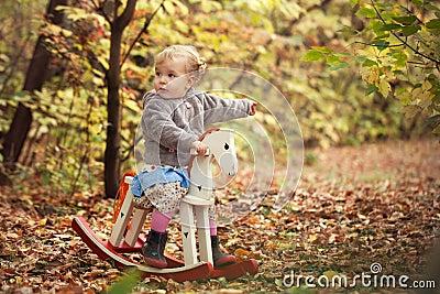 Little cute beautiful girl walks in autumn park Stock Photo