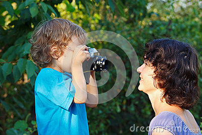 Little cute blond boy with a camera shoots mother
