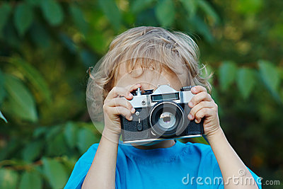 Little cute blond boy with a camera shoots you