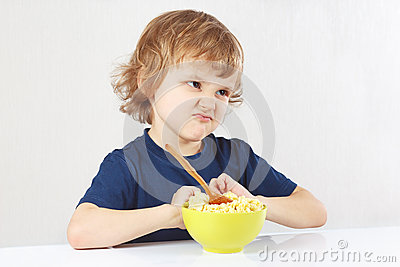 Little cute blonde boy refuses to eat porridge