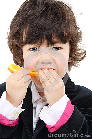 Little cute boy in coat eats orange isolated