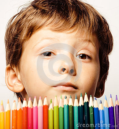 Little cute boy with color pencils close up smiling on white