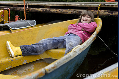 Little cute funny girl lying in boat