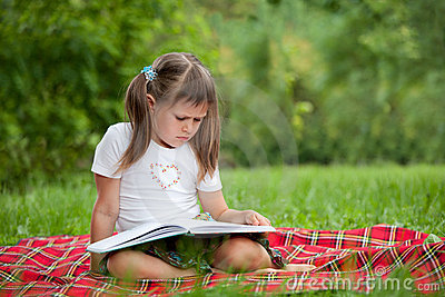 Little cute girl with book on plaid in park
