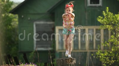 Little cute girl dancing on a stump in the yard of a country house. Happy. Little cute girl dancing on a stump in the yard of a country house stock video