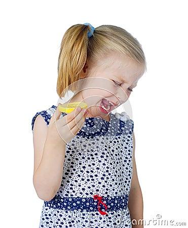 Little cute girl eating fresh lemon