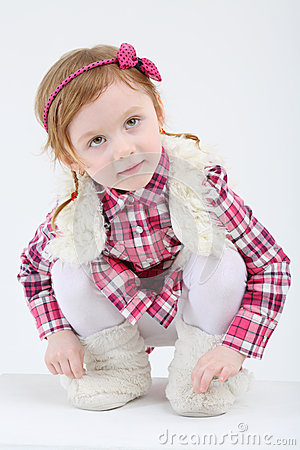 Little cute girl in fur vest and boots sits and looks up