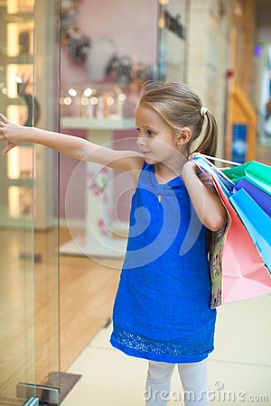 Little cute girl with packages in a large shopping