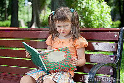 Little cute girl preschooler with book on bench