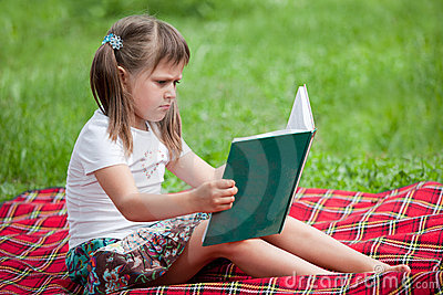 Little cute girl preschooler with book in park