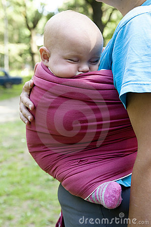 Little cute girl sleeping in sling.