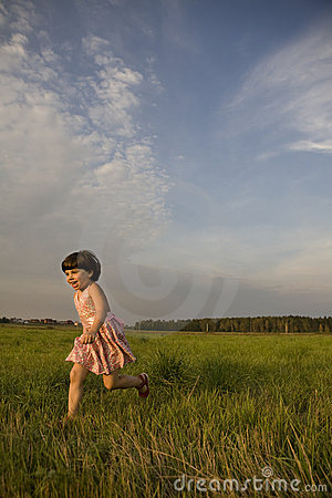 Little cute happy girl running on meadow