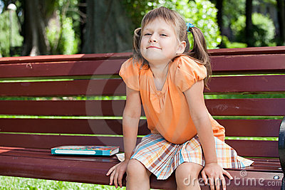 Little cute smiling girl with book on bench