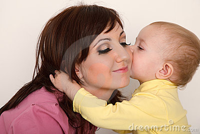 Little daughter kissing her mother.