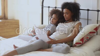 Pleasant biracial woman reading book to daughter. Little energetic child girl lying on bed with african mommy, listening to disinteresting story. Pleasant stock footage