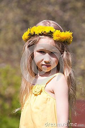 Little fair-haired girl in dandelion wreath