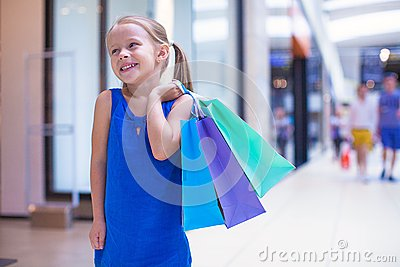 Little fashion girl with packages in a large