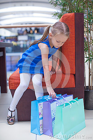 Little fashion girl sits near packages in a large
