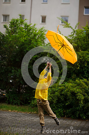 Free Little Fellow In A Bright Yellow Raincoat Flies Over The Earth With An Umbrella In Hand. Royalty Free Stock Image - 73313786