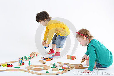 Little focused boy and girl build railway from wooden parts