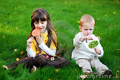 Little friends eating lollipops together on a lawn