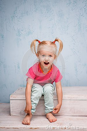 Free Little Funny Blue-eyed Girl Child Blonde With A Haircut Two Ponytails On Her Head Sitting On A Gossip On The Background Of An Old Royalty Free Stock Photos - 110025868
