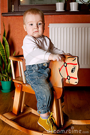 Little funny boy riding horse
