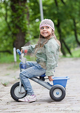 Little girl ( 4-5) on tricycle