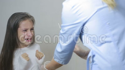 Little girl is afraid of the doctor with a syringe  baby cries afraid  injection  Adult, caucasian