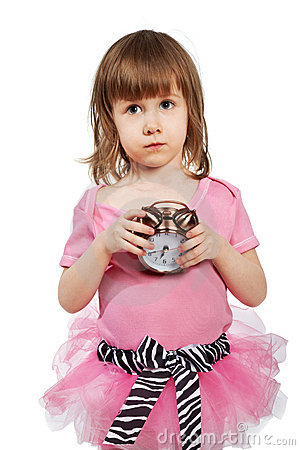 Little girl with alarm clock in hands.
