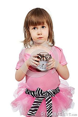 Little girl with alarm clock in hands.