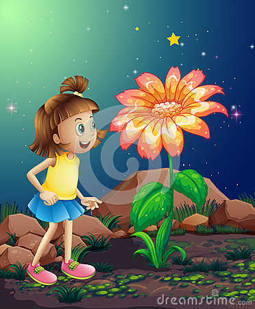 A little girl amazed by the giant flower near the rocks