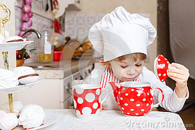 Little girl in apron in the kitchen.