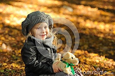 Little girl in autumn leaves