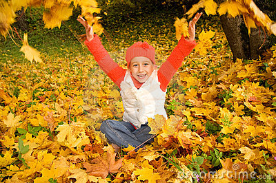 Little girl with autumn leaves outdoors